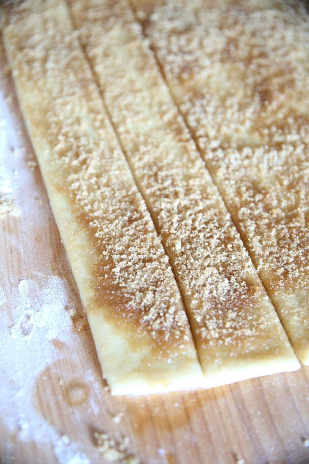 Sugar and cinnamon sprinkled on strips of dough