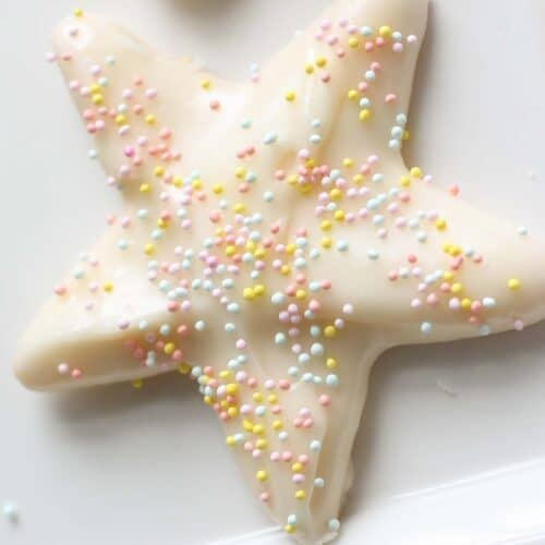 A white star shaped sugar cookie on a white surface, topped with sugar cookie icing and pastel sprinkles.