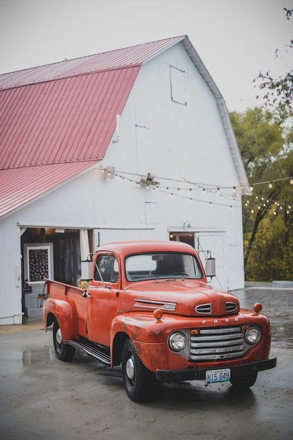 A truck is parked in front of a barn