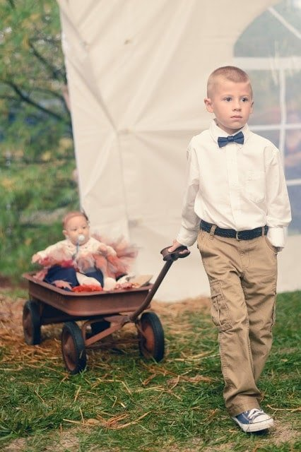 """A little boy pulling a wagon with a baby in it and a sign that says \""""Here Comes the Bride!\"""""""