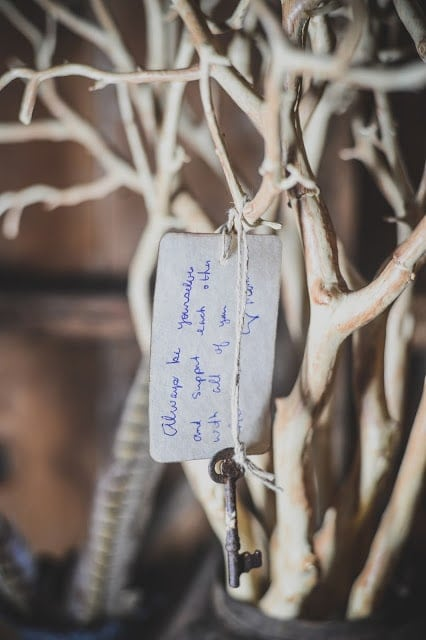 A note and a key hanging from a tree branch.