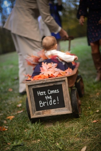 """A wagon with a baby in it and a sign that says \""""Here Comes the Bride!\"""""""