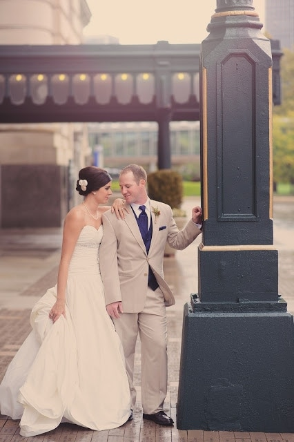 A man and a woman posing next to a pole.