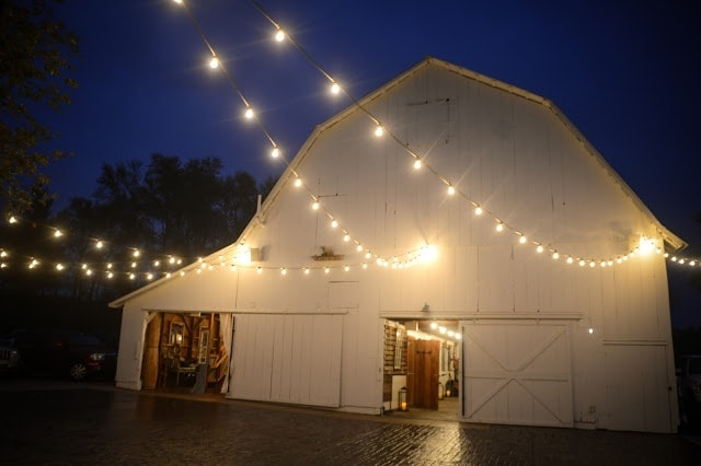 A barn with lights strung outside of it.