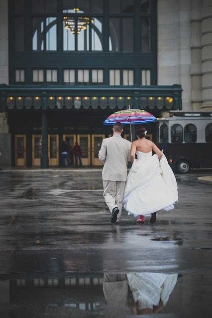 The bride and groom walking in the rain, holding an umbrella.