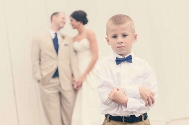 A little boy standing in front of the bride and groom.