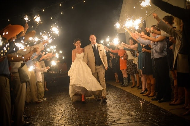 A bride and groom walking through a walkway with their friends and family holding sparklers on the side.
