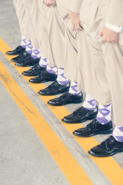 Groomsmen standing on a line wearing matching purple socks.
