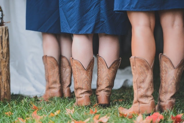 Bridesmaids standing in the grass wearing blue dresses and brown cowboy boots.