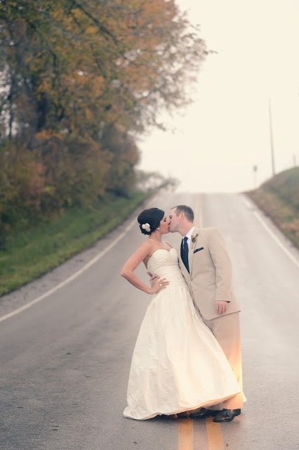 The bride and groom kissing in the middle of the street.