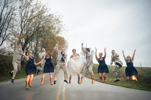 The bridal party holding hands and jumping.