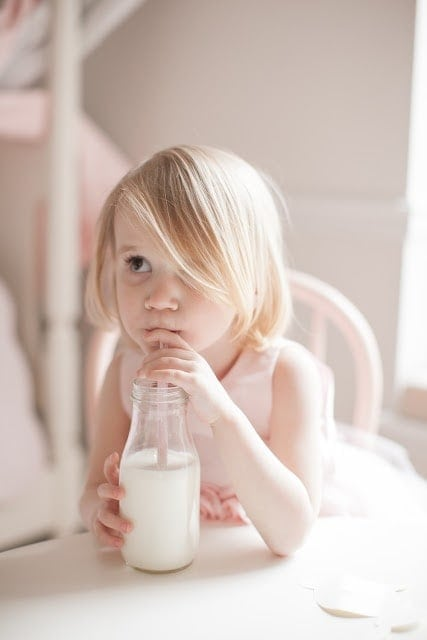 A little girl sitting at a table drinking milk.