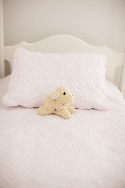 A stuffed lamb on a bed