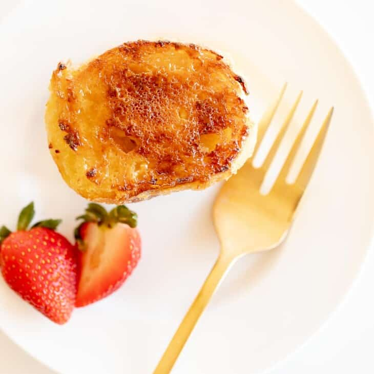 slice of creme brulee french toast on white plate with gold fork and strawberries