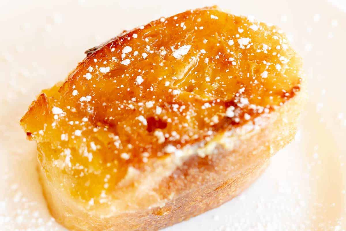 slice of french toast with creme brulee topping dusted with powdered sugar