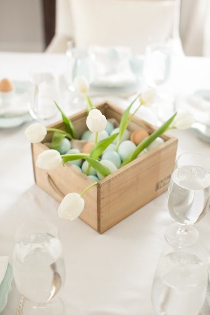 A basket of multicolored eggs and white tulips.