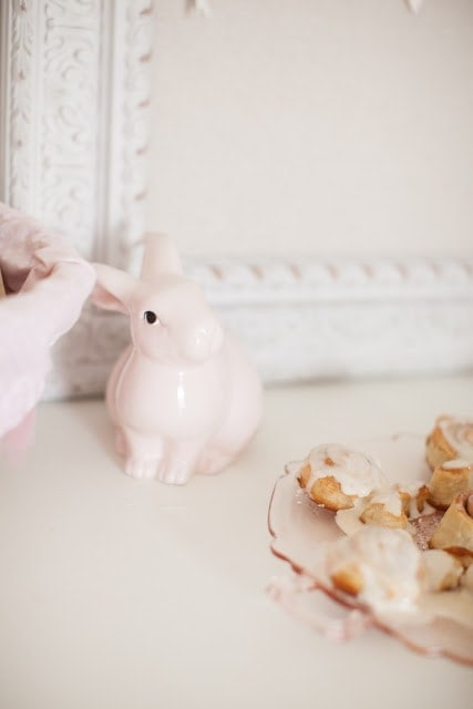 A pink ceramic bunny on a dresser.
