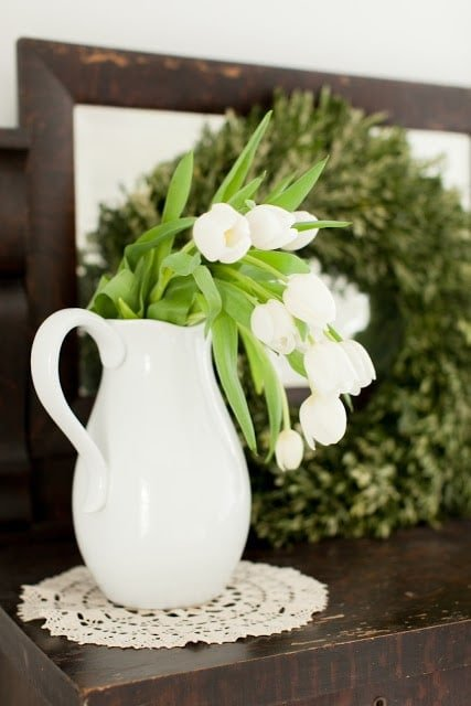 A white pitcher filled with white tulips.