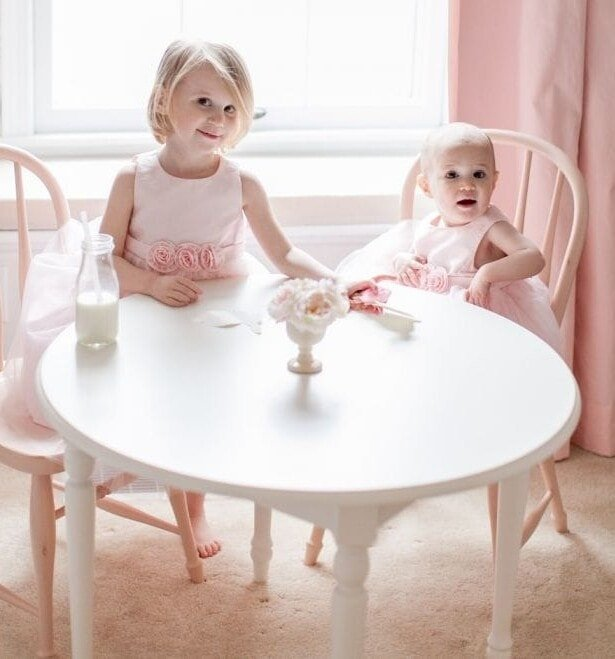 Two little girls sitting at a table