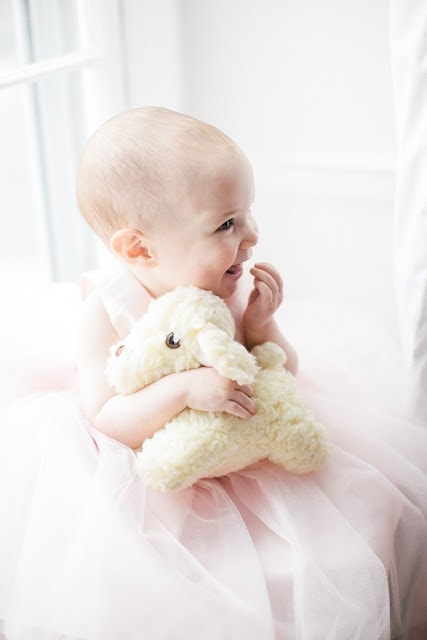 A baby holding a plush lamb