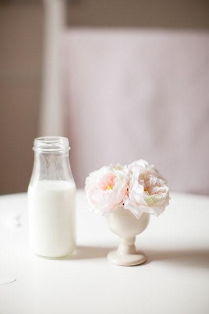 A close up of a vase and a glass of milk on a table