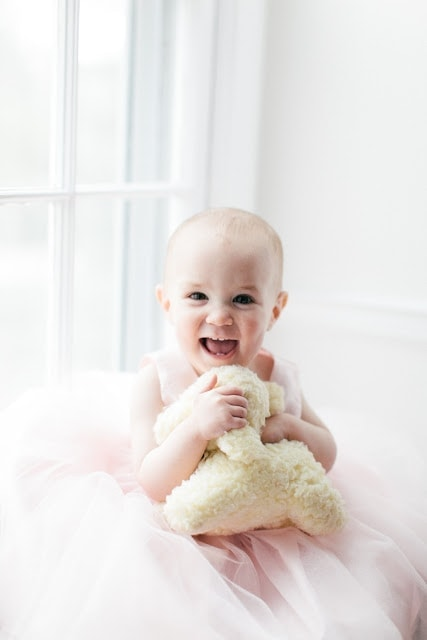 A baby laughing and playing with toys