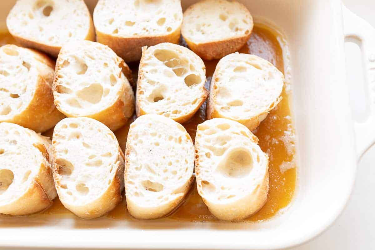 slices of french bread soaking in caramel sauce in casserole dish