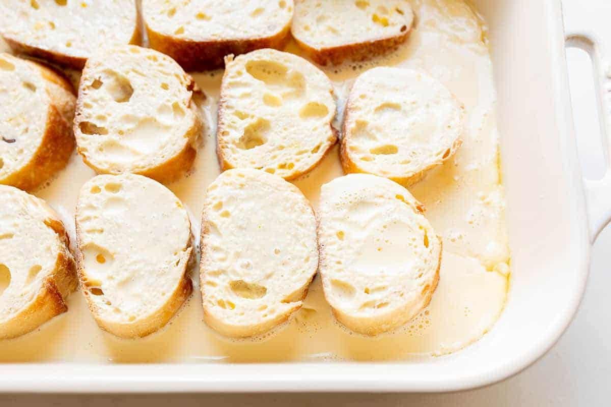 slices of french bread soaking in custard in a casserole dish