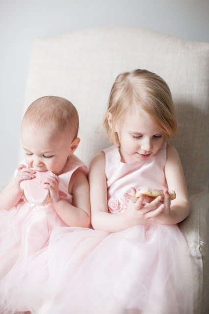 Two little girls wearing matching dresses sitting next to each other.