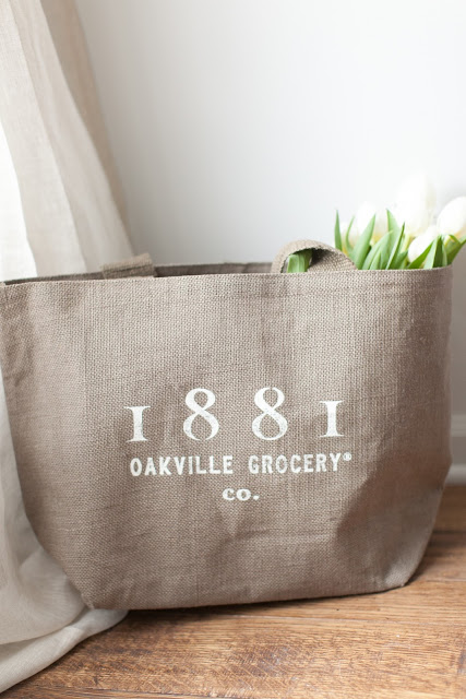 An Oakville Grocery bag filled with white tulips.