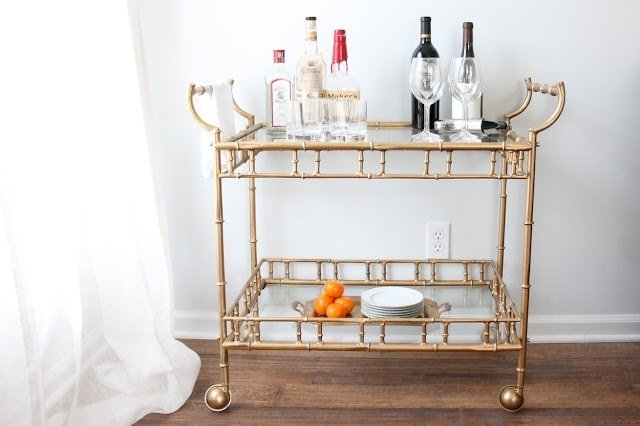 A vintage brass bar cart with glass shelves, topped with liquor bottles and glassware.