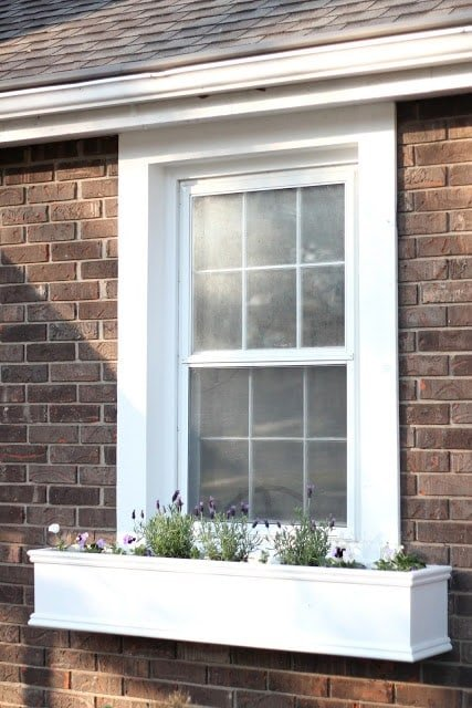 DIY wood window boxes on the front of a house filled with spring flowers