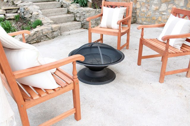Three wooden chairs next to a fire pit.