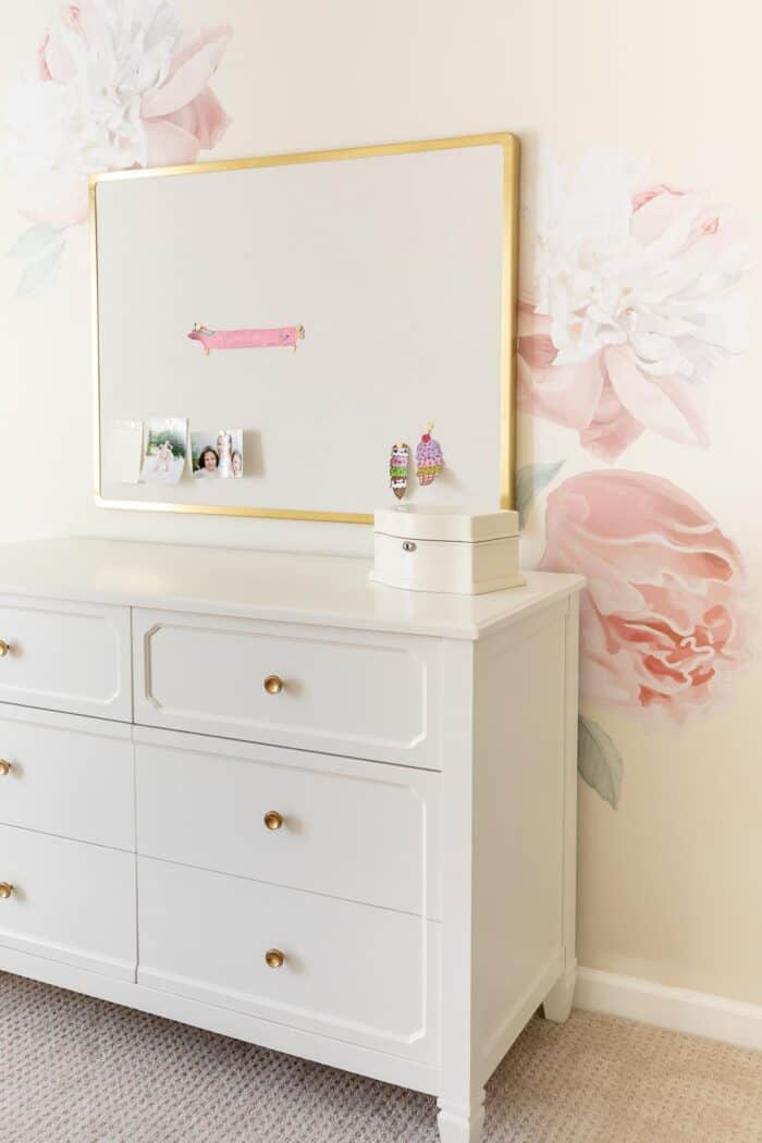 A floral decal on the wall of a pink and gold girly bedroom.