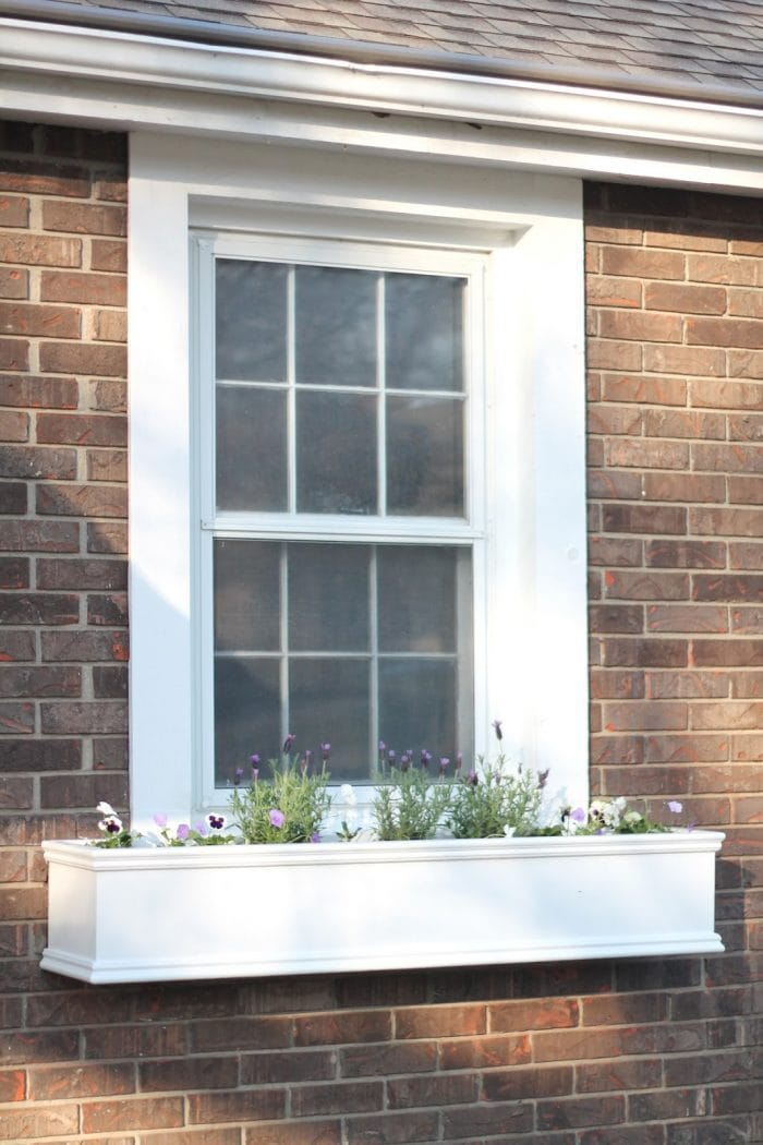 window boxes attached to red brick house with spring flowers