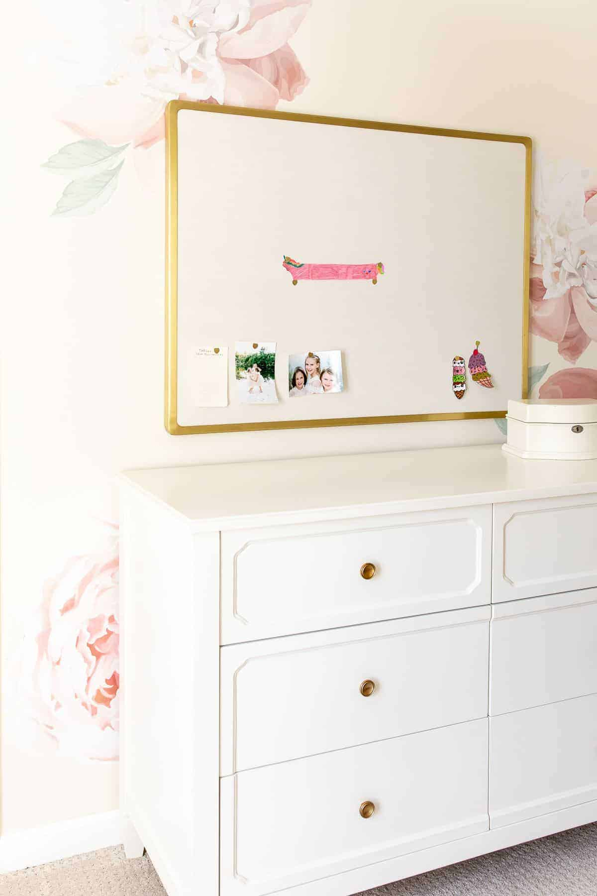 A blush pink and gold bedroom with a floral wall behind a white dresser.