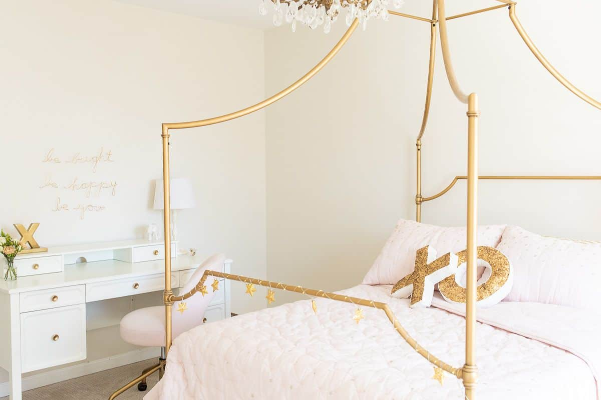 A tween girl bedroom with a gold bed and a white desk, blush pink bedding
