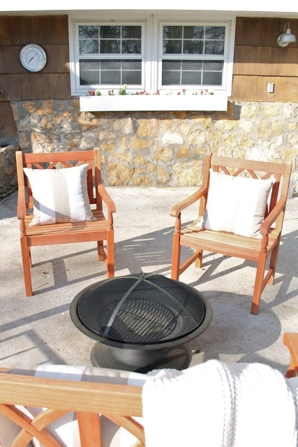 Two wooden chairs next to a fire pit.