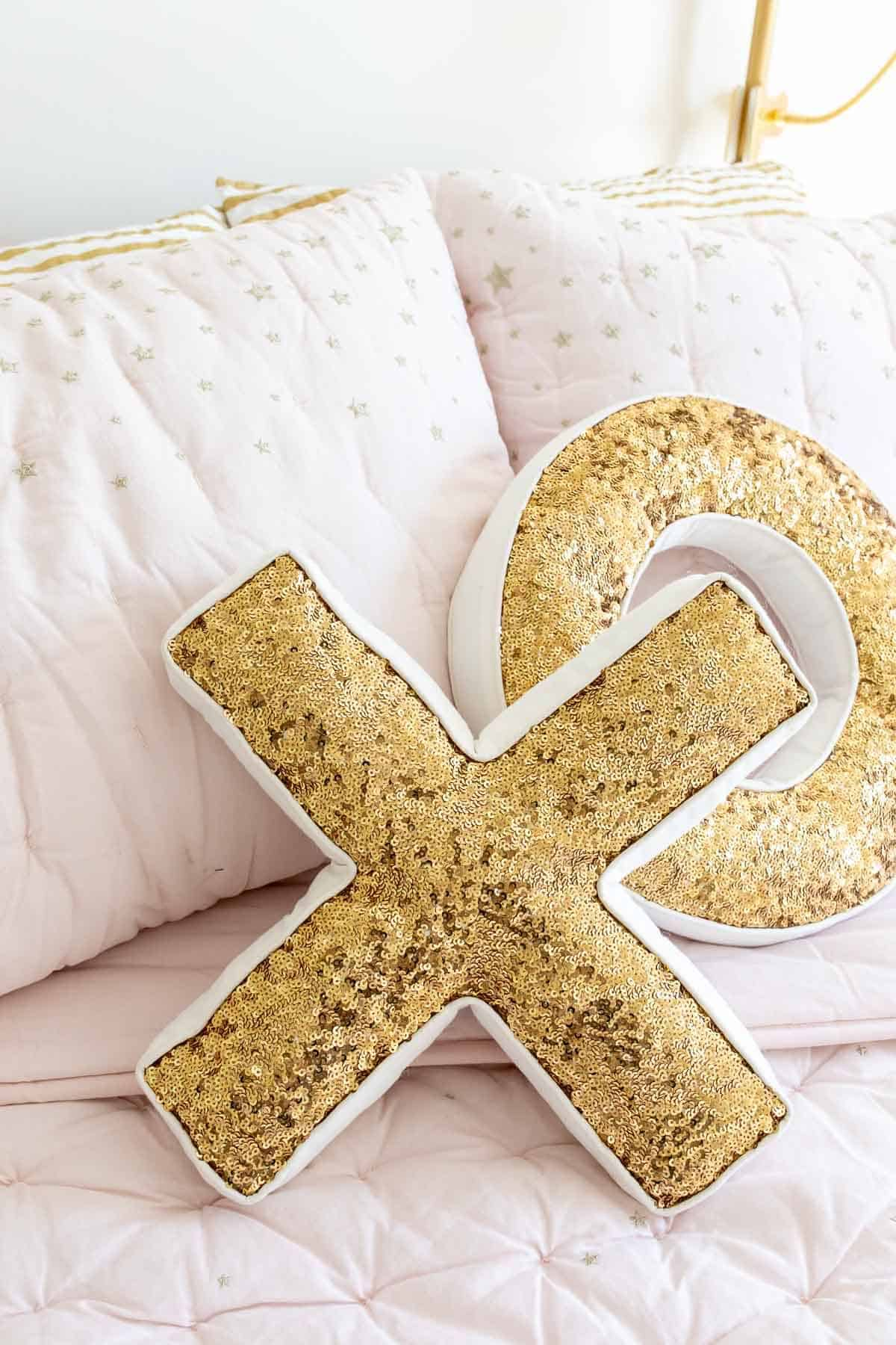 Sequined XO pillows on blush pink bedding.