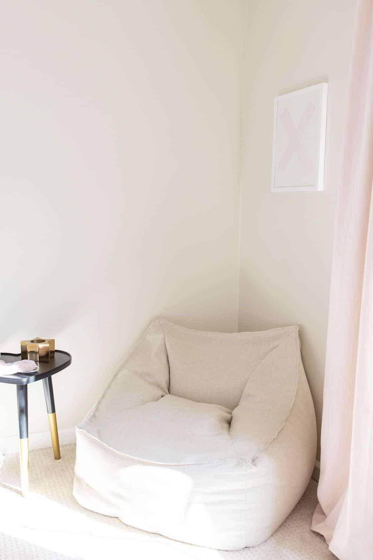A tween bedroom idea of a white lounge chair in the corner of a tween bedroom.