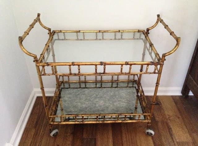 A vintage brass bar cart with glass shelves.