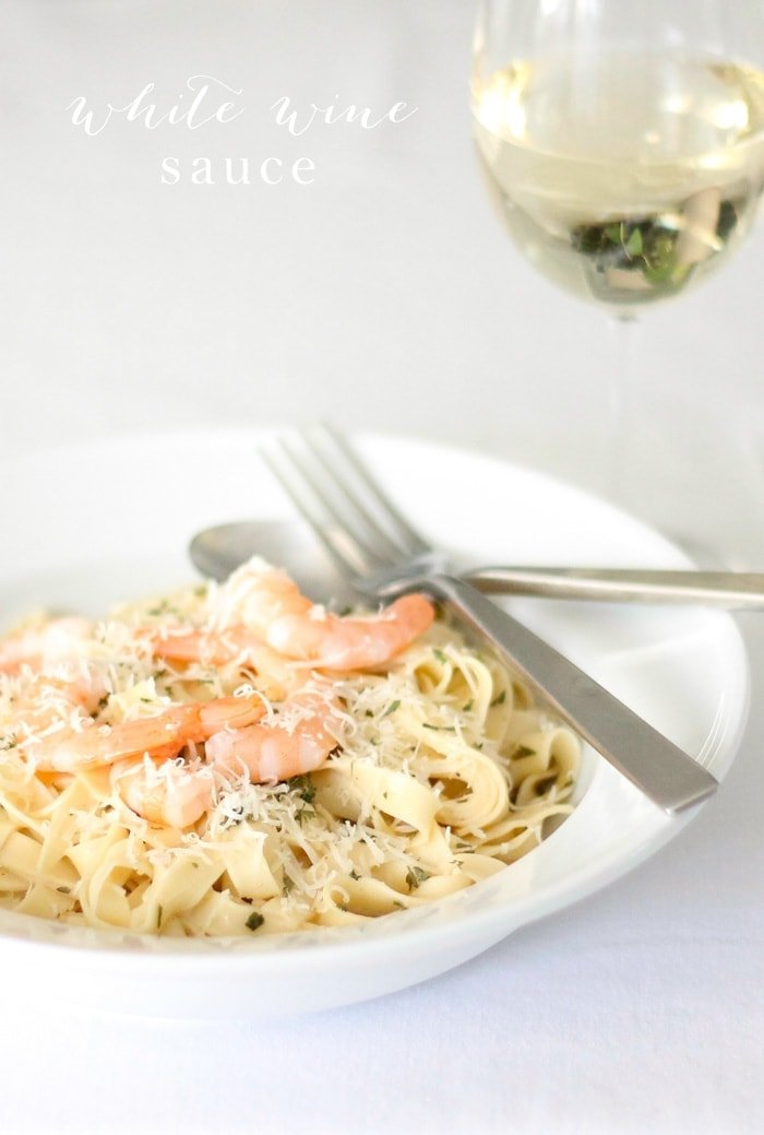 A white surface with a plate of pasta in a white wine sauce, topped with shrimp, glass of white wine to the side.