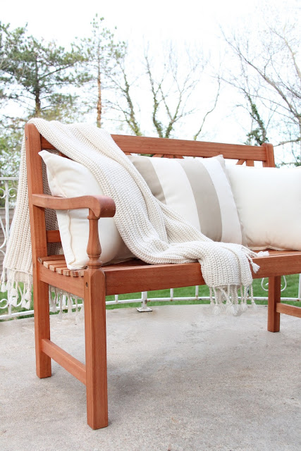 A wooden bench with decorative pillows