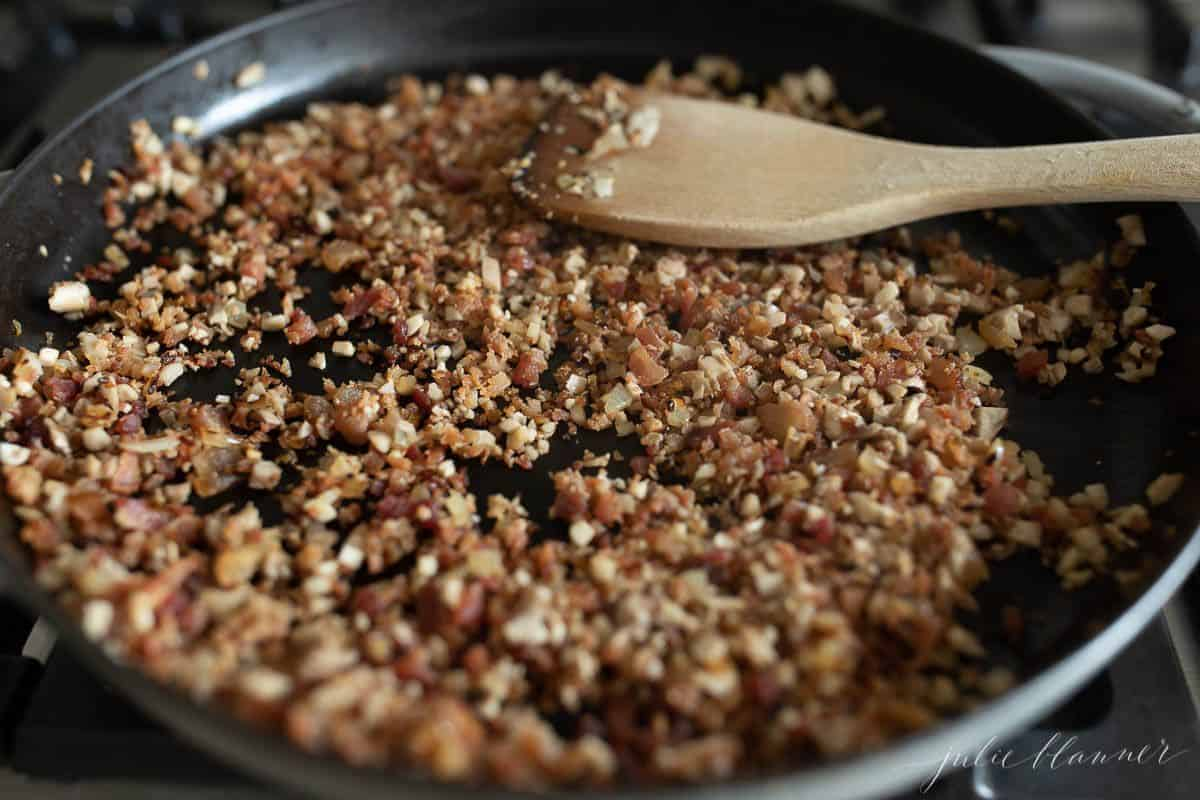 A frying pan full of diced bacon and onions with a wooden spatula to the side.