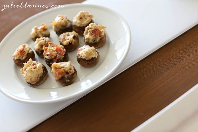 Bacon and cream cheese stuffed mushrooms served on a white plate