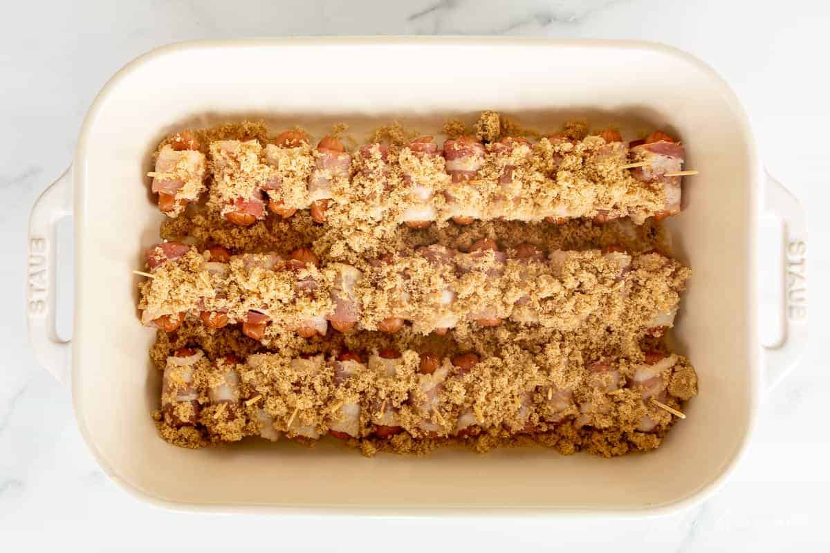cocktail weenies covered in brown sugar in white baking dish