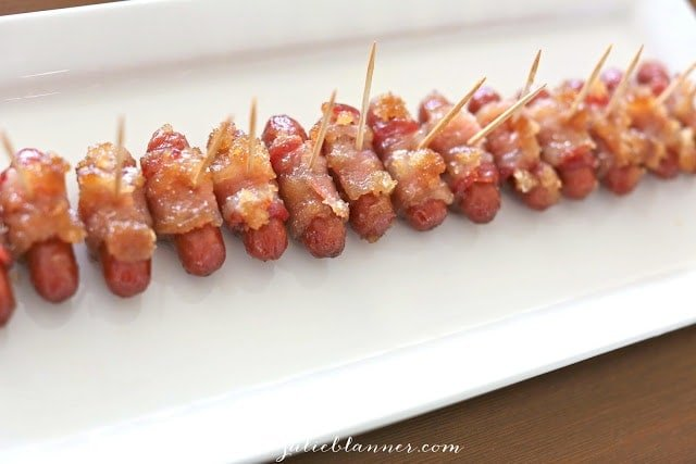 A row of bacon wrapped little smokies ready to serve