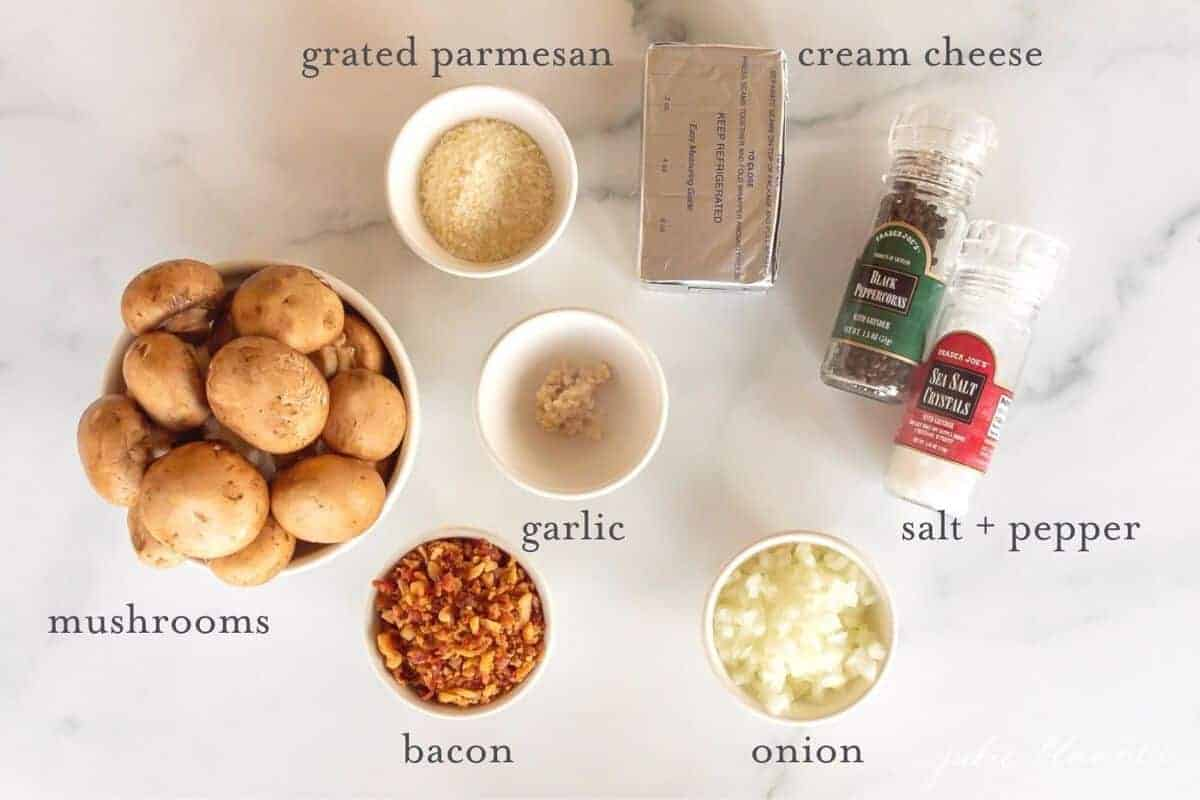 Ingredients for a stuffed mushroom recipe laid out on a white surface.
