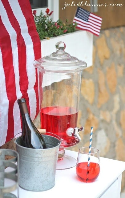 Red themed punch with a bottle of wine next to it and an American Flag in the background.