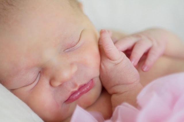 A close up of a newborn baby wearing a pink tutu.